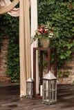 Leuchten Sie Lampe mit einem Blumenstrauß von roten und weißen Blumen durch Stockfotos