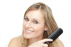 Leuchtende blonde Frau, die ihr Haar aufträgt Stockfotografie