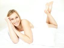 Leuchtende blonde Frau, die sich auf Bett hinlegt Stockfotografie