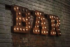 Leuchtende Buchstaben STANGE Volumetrische Buchstaben vom rostigen Metall auf einer Backsteinmauer mit einer Girlande Lizenzfreie Stockfotos