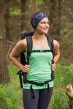 Leuchtende Frau, die in einem Wald auf einer Wanderung steht Stockfoto