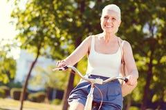 Leuchtende Frau im Ruhestand, die breit beim Radfahren grinst lizenzfreie stockfotos