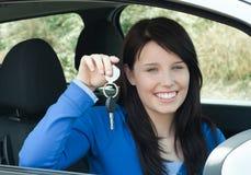 Leuchtende Jugendlichholding, die in ihrem neuen Auto sitzt Stockfoto