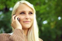 Leuchtende junge Frau auf Handy Stockbild