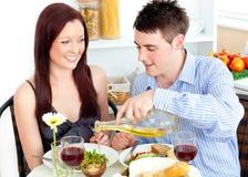 Leuchtende Paare, die zusammen in der Küche speisen Stockbilder