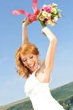 Leuchtende rote behaarte Braut hebt Blumenstrauß in der Luft an lizenzfreie stockbilder