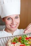 Leuchtender weiblicher Chef, der eine Pizza kocht Stockfoto