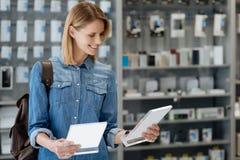 Leuchtender weiblicher Käufer, der zwei Produktinformationsplatten vergleicht Stockfotografie