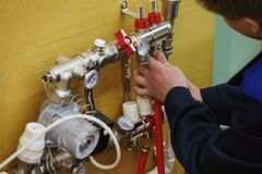 Leuchtendes Boden-Heizungs-Installations-Heizsystem Mann installieren Unterflurwarmwasserbereitungsbodenbau lizenzfreies stockfoto