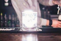 Leuchtendes Glas mit Alkoholcocktail auf dem Barzähler Stockfotografie
