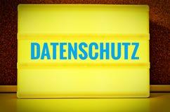 Leuchtendes Gremium mit der Aufschrift auf Deutsch Datenschutz vor einer Pinnwand, in der englischen Datenschutzerklärung, im Gel Stockbild