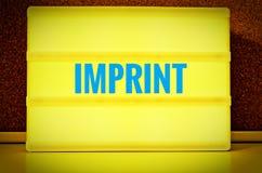 Leuchtendes Gremium mit der Aufschrift auf Deutsch Impressum vor einer Pinnwand, im englischen Impressum, im Gelb mit hellblauem  Lizenzfreie Stockfotografie