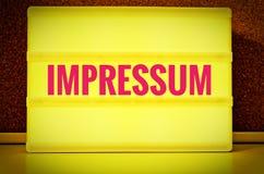 Leuchtendes Gremium mit der Aufschrift auf Deutsch Impressum vor einer Pinnwand, im englischen Impressum, im Gelb mit rosa Buchst Lizenzfreie Stockfotos