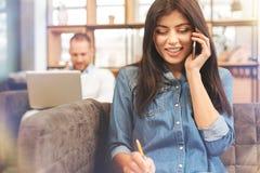 Leuchtendes weibliches startupper, das auf Telefon und dem Lächeln spricht Lizenzfreies Stockbild