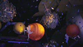 Leuchter, Bälle, Zahlen des Amors hängen im Nachtklub confetti Langsame Bewegung stock video