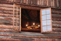 Leuchter durch ein offenes Blockhaus-Fenster Lizenzfreies Stockfoto