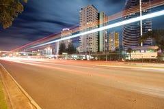 Leuchtespuren über moderner Stadt nachts Lizenzfreie Stockfotografie