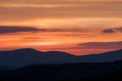 Leuchtorange-bewölkter Himmel über Gebirgsrücken Stockfotografie