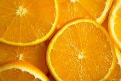 Leuchtorangehintergrund von den Scheiben von saftigen Orangen Lizenzfreie Stockfotografie
