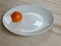 Leuchtorangesatsuma auf einer weißen Platte auf einer Tabelle stockfoto