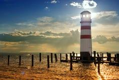 Leuchtturm auf dem Pier bei Sonnenuntergang Lizenzfreie Stockbilder