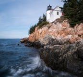 Leuchtturm auf einer felsigen Küste mit dem Zusammenstoßen bewegt in den Vordergrund wellenartig stockbilder