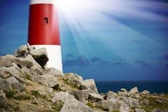 Leuchtturm auf Felsen mit Lichtstrahlen Lizenzfreie Stockfotos
