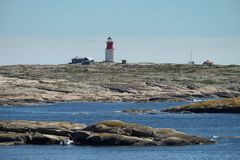 Leuchtturm auf Felsen vor der Küste stockfoto