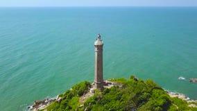 Leuchtturm auf grüner Insel auf blauer Meerwasserlandschaft, Ansicht von über fliegendem Brummen Luftlandschaftsseeleuchtturm stock video