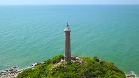 Leuchtturm auf grüner Insel in der Türkisseeluftlandschaft Hoher Leuchtturm der Brummenansicht auf Felseninsel im blauen Ozean stock video