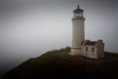 Leuchtturm auf Klippe über einem Nebel deckte Ozean ab lizenzfreie stockfotos