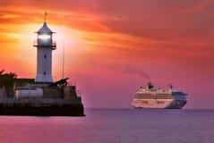 Leuchtturm in der roten Dämmerung mit Schiff Lizenzfreie Stockfotos