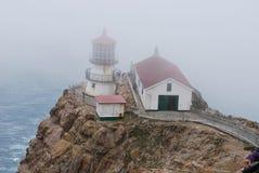 Leuchtturm durch den Nebel Stockbild