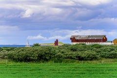 Leuchtturm, hölzerne Scheunen und Segelboot Lizenzfreies Stockfoto