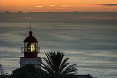 Leuchtturm im bewölkten Sonnenuntergang Stockbilder