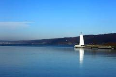 Leuchtturm im blauen See Lizenzfreies Stockbild