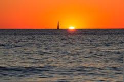 Leuchtturm im Meer während des Sonnenuntergangs Stockfotografie