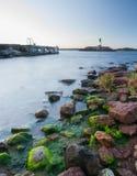 Leuchtturm mit grünen Felsen im Vordergrund Lizenzfreie Stockfotos