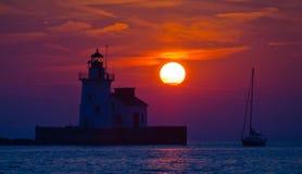 Leuchtturm nachts mit einem Segelboot gerade als der Sonne stellt ein Lizenzfreie Stockfotos