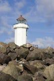 Leuchtturm-Spitzen über Felsen Stockfotografie