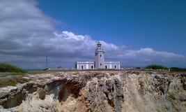 Leuchtturm und Klippe mit Wolken stockbilder