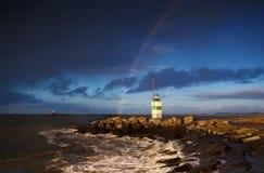 Leuchtturm und Regenbogen über Meer Stockfoto