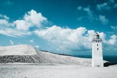 Leuchtturm und Sanddünen durch das Meer Lizenzfreie Stockbilder