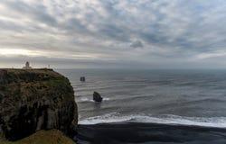 Leuchtturm und schwarzer Sand-Strand Reynisfjara in Island Morgen-Himmel und Felsen im Hintergrund Fokus in Richtung zu den niedr Stockfotos