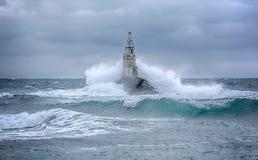 Leuchtturm und Sturm im Meer und in den großen Wellen, die in das Seelicht am Hafen von Ahtopol, Schwarzes Meer, Bulgarien breche lizenzfreie stockfotos