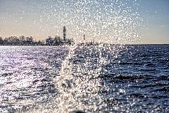 Leuchtturm und Welle spritzt an einem sonnigen Tag Stockfoto