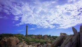 Leuchtturm unter blauem Himmel und Wolke Stockfotografie