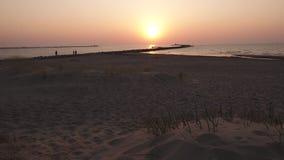 Leuchtturm während eines letzten des Sonnenuntergangs mit einer großen Sonne nah an dem Horizont und dem klaren Himmel stock video footage