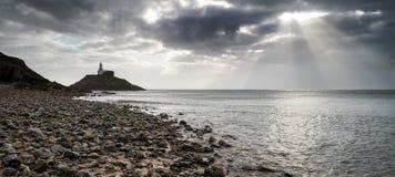 Leuchtturmlandschaft mit stürmischem Himmel über Meer mit Felsen im Vorderteil Lizenzfreies Stockfoto