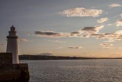 Leuchtturmschattenbild im schwermütigen Sonnenuntergang Stockbild